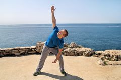 Athletic man doing stretching exercise, preparing for workout on seashore. Handsome fitness athlete doing a stretching routine. Athletic man doing stretching Royalty Free Stock Images