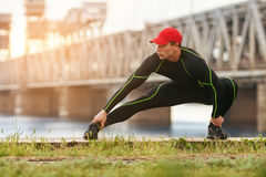 Athletic man doing stretching exercises, outdoor. Active male working out outside on the background of the bridge.  Stock Photo