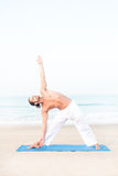 Athletic Man Doing Yoga on a Mat at the Beach Stock Photography