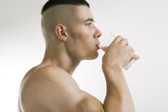 Athletic man drink protein shake. Athletic young man with protein shake, isolated on white stock images