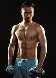 Athletic man with dumbbells on the black background Royalty Free Stock Photos