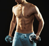 Athletic man with dumbbells on the black background Stock Photo