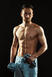 Athletic man with dumbbells on the black background Royalty Free Stock Photo