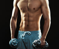 Athletic man with dumbbells on the black background Stock Photography