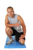 Athletic man on an exercise mat drinking water Royalty Free Stock Photos