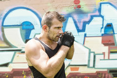 Athletic man fighter in boxing pose, urban style. Stock Photo
