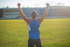 Athletic man is happy and rejoicing at the stadium Stock Photos