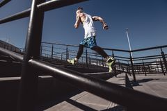 Athletic man with headband on his head dressed in the white t-shirt, black leggings and blue shorts is running up the stock image