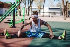 Athletic man with headband on his head and tattoos dressed in the white t-shirt, black leggings and blue shorts is doing stock photo