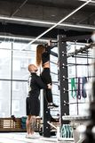 Athletic man helps young slender girl dressed in black sorts clothes to do pull up on the bar in the gym royalty free stock images