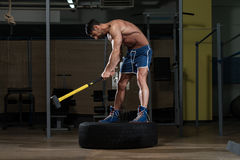Athletic Man Hits Tire Royalty Free Stock Image
