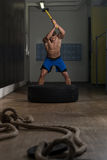 Athletic Man Hits Tire Royalty Free Stock Photo