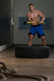 Athletic Man Hits Tire Stock Photography
