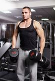 Athletic man holding heavy dumbbells Royalty Free Stock Images