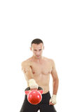 Athletic man holding and lifting up red kettlebell weight Stock Photography