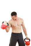 Athletic man holding and lifting up red kettlebells weights one Stock Photography