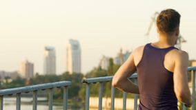 Athletic man jogging along bridge in big city, healthy way of life, slow-motion. Stock footage stock video footage
