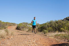 Athletic man jogging on country trail Royalty Free Stock Photos