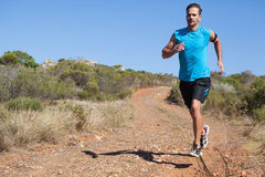 Athletic man jogging on country trail Stock Photo