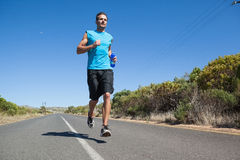 Athletic man jogging on open road holding bottle Royalty Free Stock Images