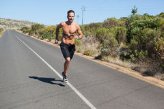 Athletic man jogging on open road with monitor around chest Royalty Free Stock Photo
