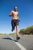 Athletic man jogging on open road with monitor around chest Royalty Free Stock Image