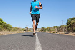 Athletic man jogging on open road Royalty Free Stock Photo