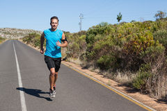 Athletic man jogging on open road Royalty Free Stock Image