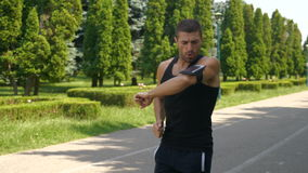Athletic man jogging in a park and checking smart phone fitness tracker app. Athletic man jogging in the park and checking smart phone fitness tracker app stock video footage