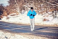 Athletic man jogging and training outdoor in park with snow Stock Images