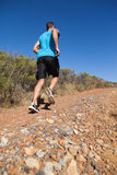 Athletic man jogging up country trail Stock Photography