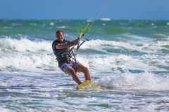 Athletic man jump on kite surf board sea waves Stock Photos
