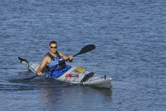 Athletic man in kayak. Athletic man is showing off his kayaking skills at Mission Bay, San Diego under a warm light of late summer afternoon Stock Photos