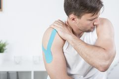 Athletic man during kinesiotherapy Royalty Free Stock Photos
