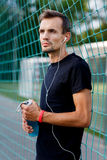 Athletic man listening to music and holding water bottle outdoors stock photos