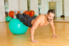 Athletic man making push ups. Athletic man in sport club making push ups on a stability ball stock photo