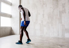 Athletic man making step ahead. Warming up. Concentrated african young sporty guy is moving forward. He is looking down. Copy space in right side Stock Photo