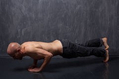 Athletic man with naked torso doing push-ups. Stock Photos