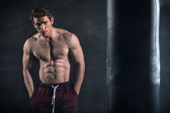 Athletic man with naked torso near concrete wall Stock Images