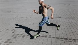 Athletic man with a naked torso with tattoos and headband on his head dressed in the black leggings and blue shorts runs royalty free stock image