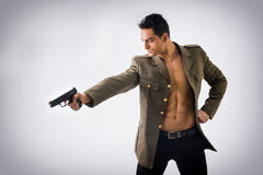 Athletic Man in Open Military Jacket Holding Gun Stock Photos