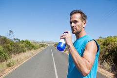 Athletic man on open road taking a drink Stock Photos
