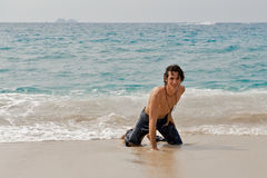 Athletic man playing on the beach in Costa Rica. Athletic young man on the beach preparing to stand up after swimming in the ocean waves Royalty Free Stock Photo