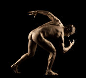 Athletic man posing nude in dark Royalty Free Stock Photography
