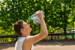 Athletic Man Pouring Water from Bottle onto Face Royalty Free Stock Image