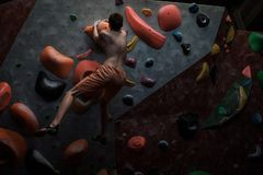 Athletic man practicing in a bouldering gym. Athletic man practising in a bouldering gym stock image