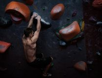 Athletic man practicing in a bouldering gym. Athletic man practising in a bouldering gym royalty free stock photos