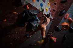 Athletic man practicing in a bouldering gym. Athletic man practising in a bouldering gym royalty free stock image