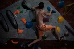 Athletic man practicing in a bouldering gym. Athletic man practising in a bouldering gym stock photos