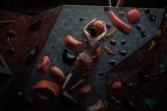 Athletic man practicing in a bouldering gym. Athletic man practising in a bouldering gym royalty free stock images